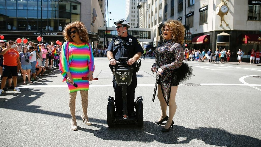 Cincinnati Police officer Steve Edwards laughs with Brooklyn Steele-Tate, left, and Tyese Rainz before the start of the Cincinnati Pride parade Saturday, June 25, 2016, in Cincinnati. Authorities planned tight security for Cincinnati's parade and festival events celebrating Gay, Lesbian, Bisexual and Transgender Pride Month. (Cara Owsley/The Cincinnati Enquirer via AP)  MANDATORY CREDIT;  NO SALES