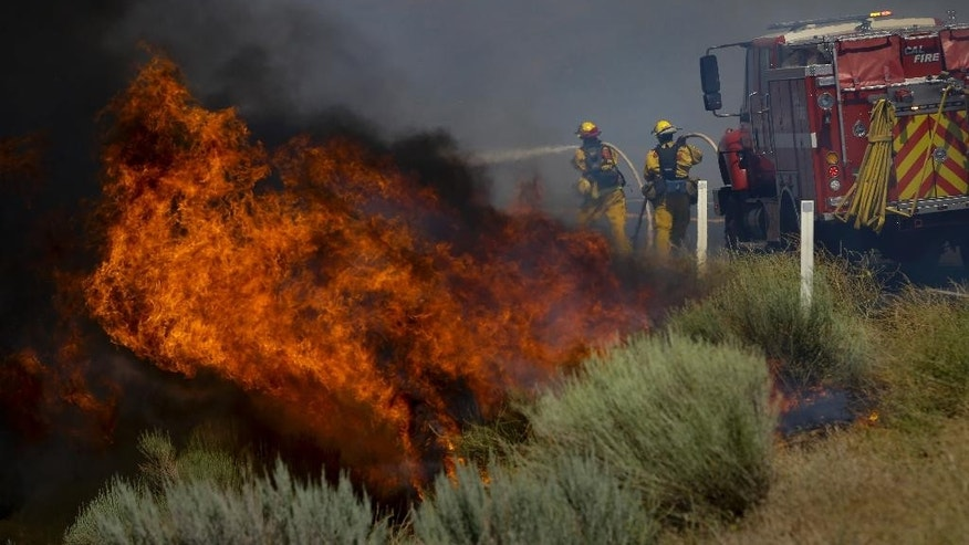 Firefighters battle a wildfire burning along Highway 178 near Lake Isabella, Calif., Friday, June 24, 2016. The wildfire that roared across dry brush and trees in the mountains of central California gave residents little time to flee as flames burned homes to the ground, propane tanks exploded and smoke obscured the path to safety. (AP Photo/Jae C. Hong)