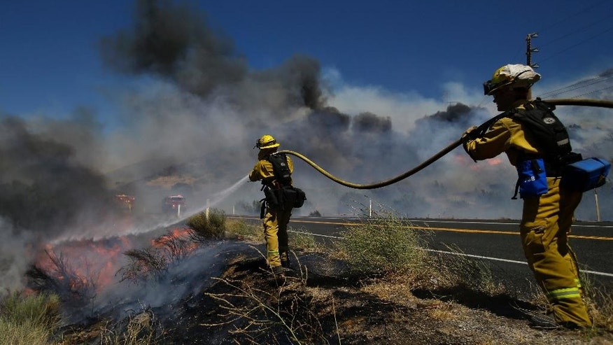 Firefighters put out a spot fire as they continue to battle a wildfire burning along Highway 178 near Lake Isabella, Calif., Friday, June 24, 2016. The wildfire that roared across dry brush and trees in the mountains of central California gave residents little time to flee as flames burned homes to the ground, propane tanks exploded and smoke obscured the path to safety. (AP Photo/Jae C. Hong)