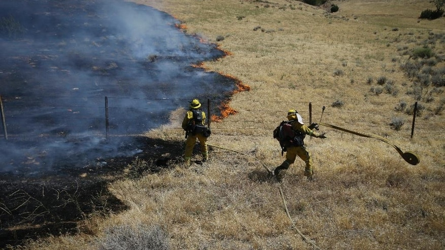 Firefighters prepare water hoses to battle a wildfire burning along Highway 178 near Lake Isabella, Calif., Friday, June 24, 2016. The wildfire that roared across dry brush and trees in the mountains of central California gave residents little time to flee as flames burned homes to the ground, propane tanks exploded and smoke obscured the path to safety. (AP Photo/Jae C. Hong)