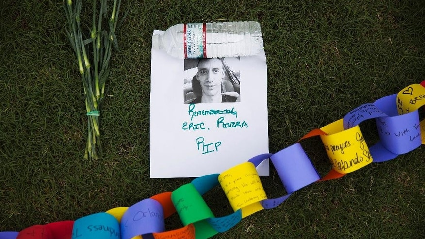 FILE. In this June 13, 2016 file photo, a remembrance to Eric Rivera who was killed in the mass shooting at the Pulse nightclub sits amongst a makeshift memorial to the all the victims, in Orlando, Fla. A year after New York City's storied gay pride parade celebrated a high point with the legalization of gay marriage nationwide, the atmosphere this year couldn't be more different. Parades in New York and other major cities Sunday will feature increased security, anti-violence messages and tributes to those killed in this month's massacre at a gay nightclub in Florida. (AP Photo/David Goldman, FILE)