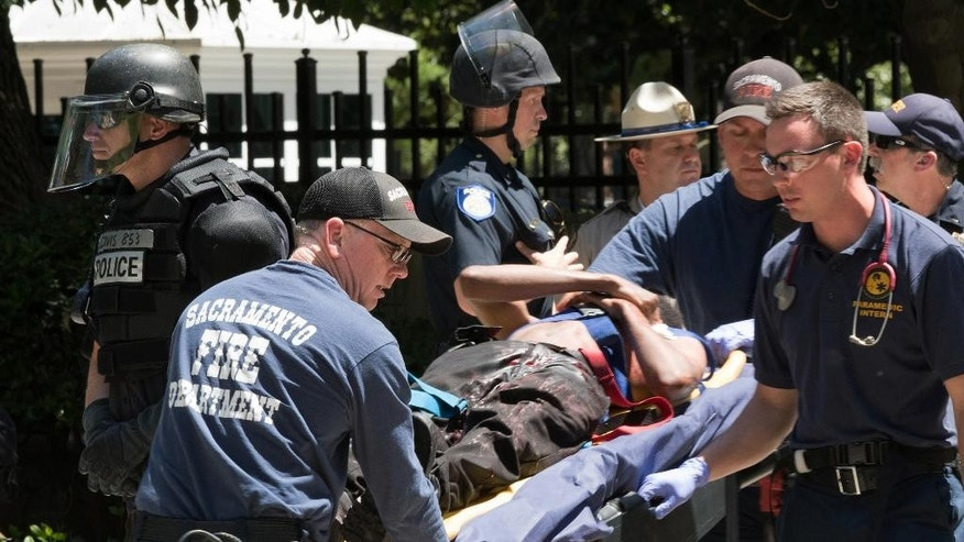 Paramedics rush a stabbing victim away on a gurney Sunday, June 26, 2016, after members of right-wing extremists groups holding a rally outside the California state Capitol building in Sacramento clashed with counter-protesters, authorities said. Sacramento Police spokesman Matt McPhail said the Traditionalist Workers Party had scheduled and received a permit to protest at noon Sunday in front of the Capitol. McPhail said a group showed up to demonstrate against them. (AP Photo/Steven Styles)