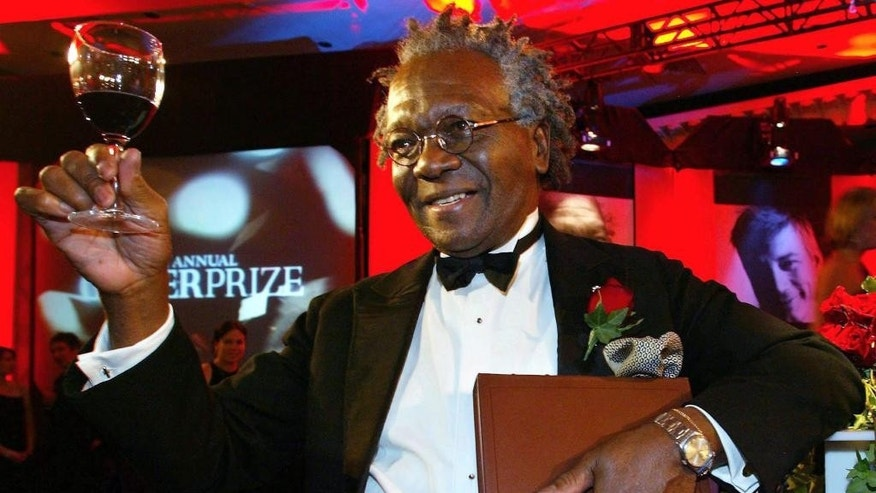 In this Nov. 5, 2002 photo, Giller Prize winner Austin Clarke hoists a glass as he holds a copy of his book the Polished Hoe after winning the $25,000 literary prize at the Four Seasons Hotel in Toronto. Clarke, the award-winning Barbadian-born author who wrote about the immigrant experience and being black in Canada, has died at age 81. (Kevin Frayer/The Canadian Press via AP) MANDATORY CREDIT