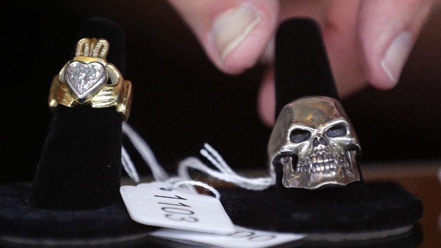 """Auctioneer Bob Sheehan reaches for a silver skull ring, which is on display next to a diamond claddagh ring, that are among items belonging to James """"Whitey"""" Bulger and Catherine Greig, which will be auctioned off this weekend at the Boston Convention Center, Friday, June 24, 2016, in Boston. The proceeds will be divided among the families of Bulger's victims. (AP Photo/Charles Krupa)"""