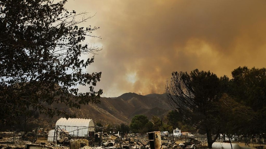The remains of mobile homes devastated by a wildfire are seen in the foreground as smoke rises over a mountain, Saturday, June 25, 2016, in South Lake, Calif. (AP Photo/Jae C. Hong)