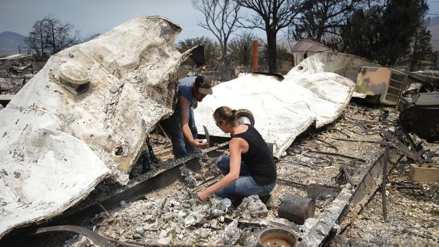 Douglas Nelson, left, shows his wife, Amy, an item he found as they survey the remains of their home devastated by a wildfire, Saturday, June 25, 2016, in South Lake, Calif. The couple said they lost everything including their dog. (AP Photo/Jae C. Hong)