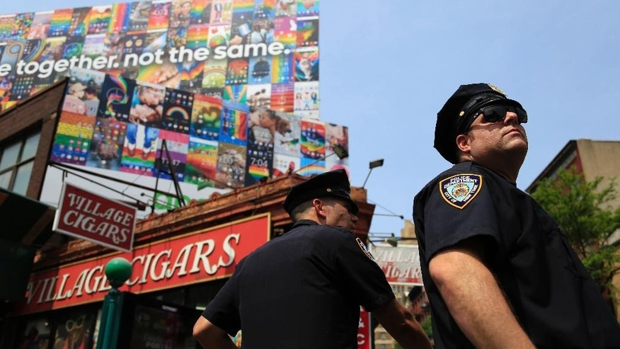 Police officers stand along the route of the NYC Pride Parade in New York, Sunday, June 26, 2016. Onlookers lined up early and police ramped up security Sunday to get ready for New York City's famous gay pride parade, a march down Fifth Avenue that would be both celebration of barriers breached and a remembrance of the lives lost in a shooting at a gay nightclub in Florida.  (AP Photo/Seth Wenig)