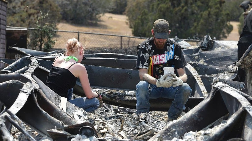 Lucas Martin stares at a cup found in the ashes of his fire ravaged home in South Lake, Calif., Sunday, June 26, 2016. Martin's home was among the more than 200 homes and buildings destroyed by the fire that swept through the area near Lake Isabella, Calif. At right is Emily Fryer who help Martin sift through the rubble. (AP Photo/Rich Pedroncelli)