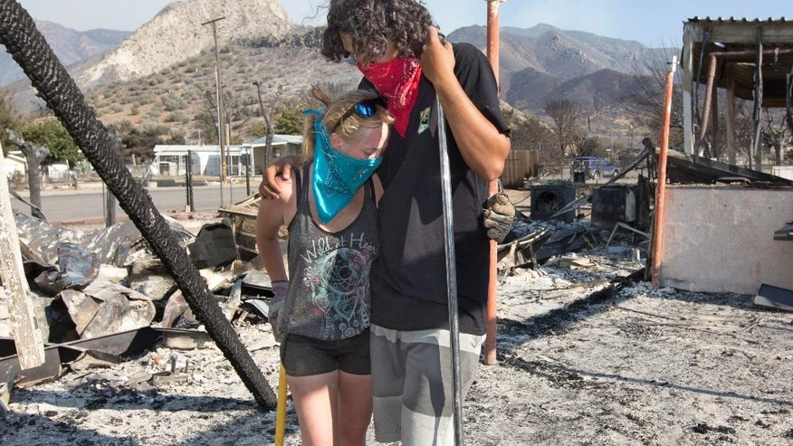 Brittany Thompson and Aquivo Sun hug each other after going through the burned out remains of the their home Sunday, June 26, 2016, in South Lake, Calif. A deadly wildfire in central California has burned hundreds of homes. (AP Photo/Rich Pedroncelli)