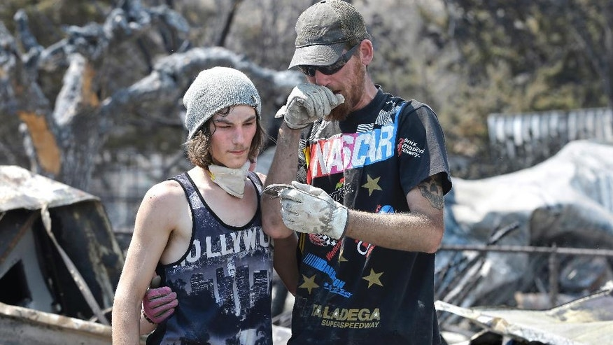 Lucas Martin, right, is overcome by emotion, Sunday June 26, 2016, as he shows his stepson Nathan Looper, an heirloom belt buckle he thought was destroyed at his home in South Lake, Calif. The buckle belonged to Martin's best friend who had left it at the home when he went to work on day the home was destroyed. Martin promised his roommate he would find it. (AP Photo/Rich Pedroncelli)