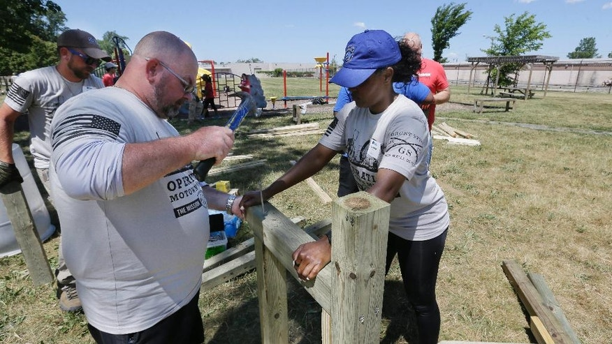 Veterans Thomas Hart, left, and Damika Wallace work on building outdoor furniture at the Beland Manning Park, Monday, June 27, 2016, in Detroit. Hundreds of veterans are in the financially troubled city for a week to rebuild areas that have been neglected by poverty, crime and a lack of resources. It's the latest and largest effort undertaken by St. Louis-based The Mission Continues, which encourages and aids volunteerism by disabled and wounded veterans. (AP Photo/Carlos Osorio)