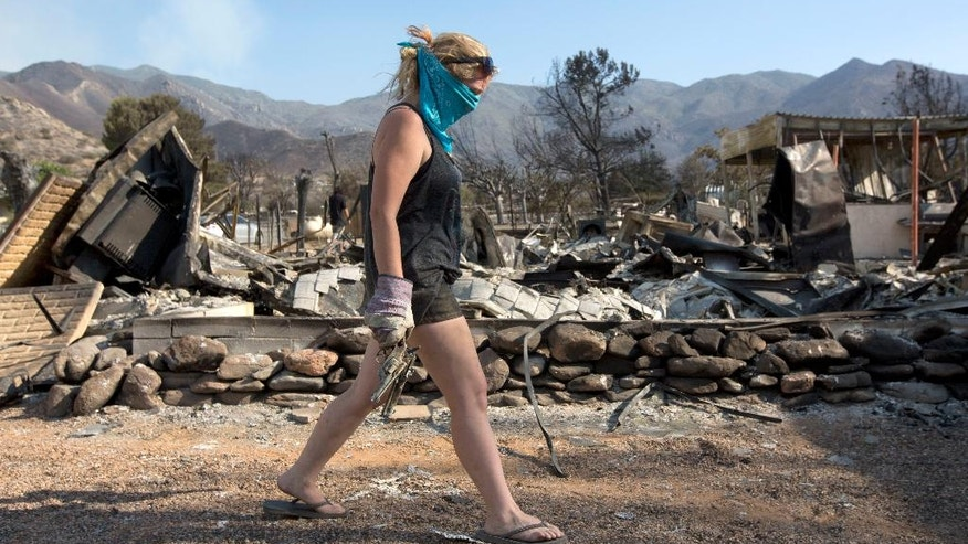 Brittany Thompson carries a pair of pistols found in the ashes of the burned out home she shared with her boyfriend, Aquivo Sun, in South Lake, Calif., on Sunday, June 26, 2016. A deadly wildfire in central California has burned hundreds of homes. (AP Photo/Rich Pedroncelli)