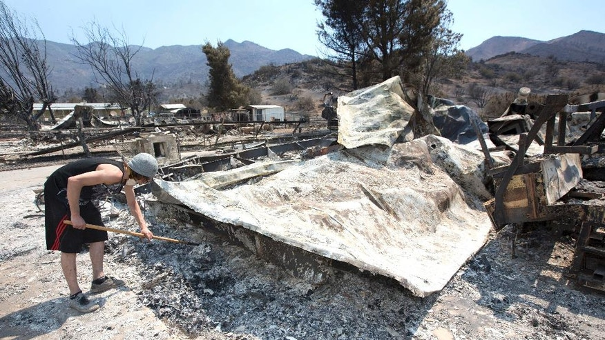 Nathan Looper uses a hoe to sift through the ashes of the home of his stepfather, Lucas Martin, Sunday, June 26, 2016, in South Lake, Calif. Martin's home was among the more than 200 homes and buildings destroyed by the fire that swept through the area near Lake Isabella, Calif. (AP Photo/Rich Pedroncelli)