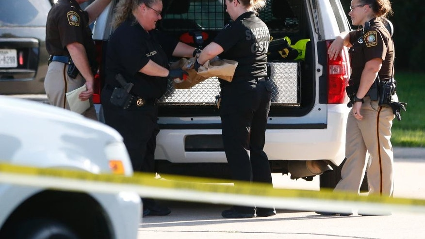 In this Friday, June 24, 2016 photo, Fort Bend County Sheriffs department crime scene members bag a gun for evidence in a shooting at Blanchard Grove and Remson Hollow in Katy, Texas. Officials said a woman shot her two adult daughters - killing one of them at the scene - before she was fatally shot by a responding police officer. (Karen Warren/Houston Chronicle via AP)