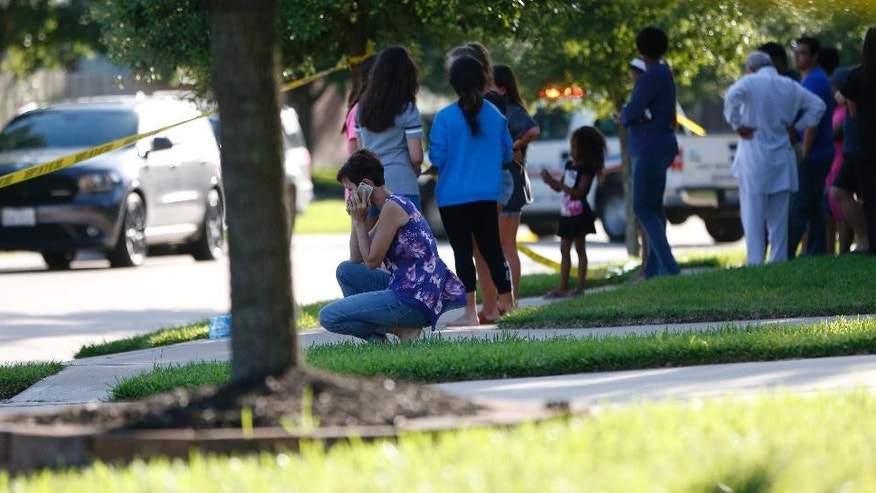 In this Friday, June 24, 2016 photo, neighbors gather to watch as Fort Bend County Sheriffs department investigates a shooting at Blanchard Grove and Remson Hollow in Katy, Texas. Officials said a woman shot her two adult daughters - killing one of them at the scene - before she was fatally shot by a responding police officer. (Karen Warren/Houston Chronicle via AP)