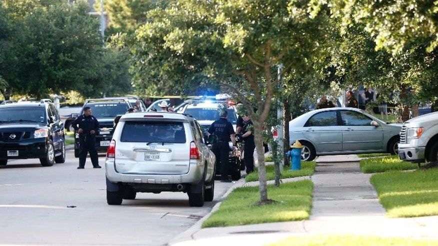 In this Friday, June 24, 2016 photo, Fort Bend County Sheriffs department investigate a shooting at Blanchard Grove and Remson Hollow in Katy, Texas. Officials said a woman shot her two adult daughters - killing one of them at the scene - before she was fatally shot by a responding police officer. (Karen Warren/Houston Chronicle via AP)