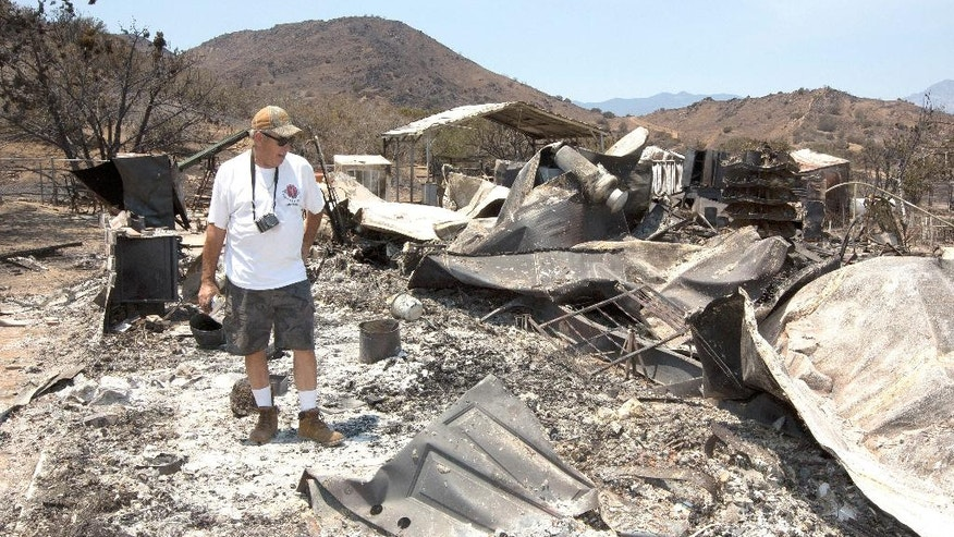 Steve Keeling walks through the ashes of his fire ravaged home, Monday, June 27, 2016, in South Lake, Calif. The home was one of the homes and structures that were destroyed by the fire that started Thursday, near Lake Isabella, Calif. (AP Photo/Rich Pedroncelli)