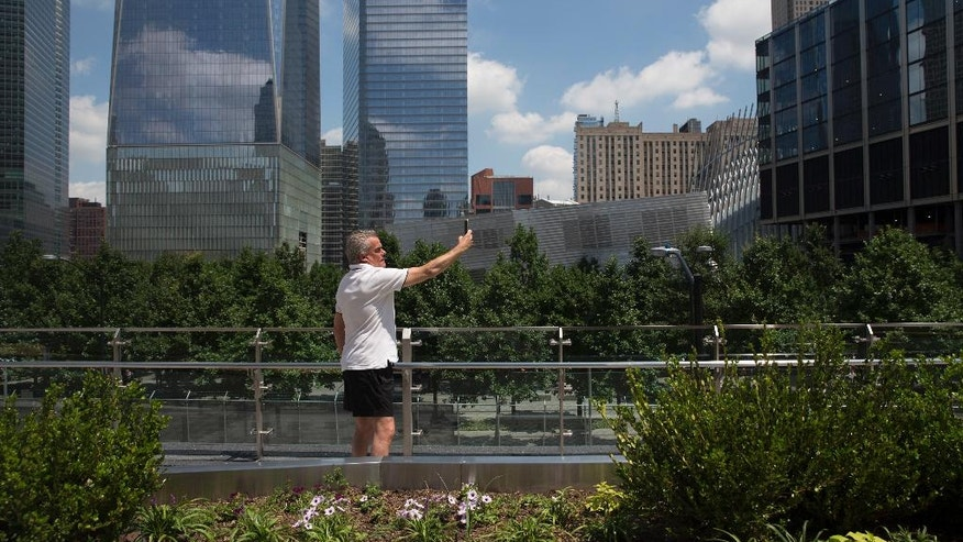 A visitor to Liberty Park take a selfie, Wednesday, June 29, 2016, in New York. The one-acre, elevated Liberty Park opened to the public Wednesday. Built on top of a security center, it overlooks the memorial to those who died in the Sept. 11 attacks. (AP Photo/Mary Altaffer)