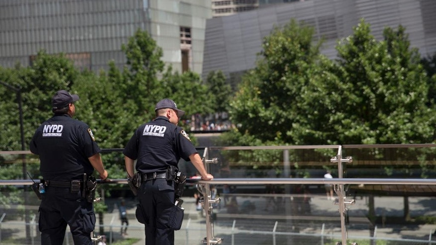 Police officers with the counterterrorism unit stand guard in Liberty Park overlooking the the memorial Wednesday, June 29, 2016, in New York. The one-acre, elevated Liberty Park opened to the public Wednesday. Built on top of a security center, it overlooks the memorial to those who died in the Sept. 11 attacks. (AP Photo/Mary Altaffer)