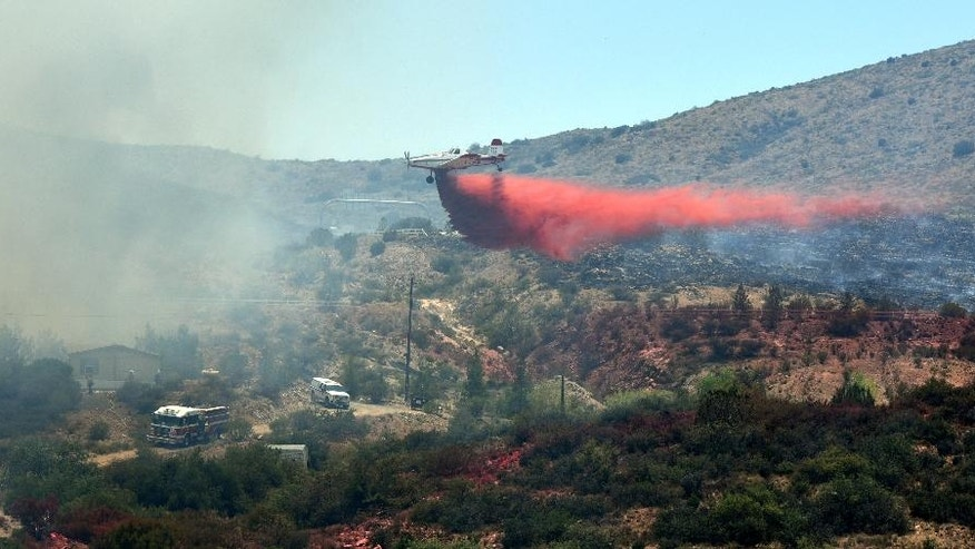 A single engine air tanker drops a load of retardent to create fire lines on the Bug Creek Fire near Cordes Lakes, Ariz., Tuesday, June 28, 2016.  (Les Stukenberg/The Daily Courier via AP) MANDATORY CREDIT