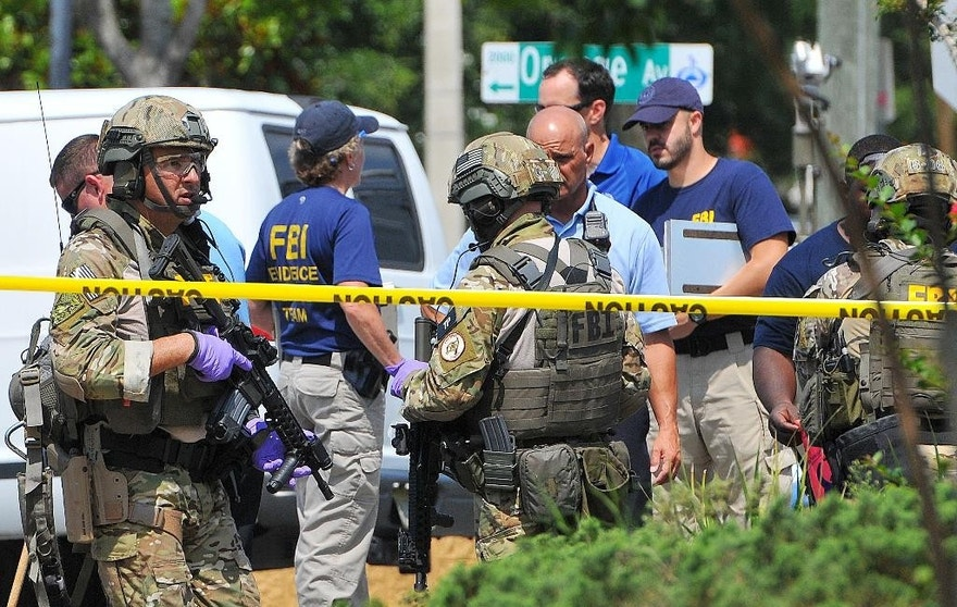 "FILE - In this June 12, 2016 file photo, FBI, Orlando Police Department and personnel from the Orange County Sheriff's Office investigate the attack at the Pulse nightclub in Orlando, Fla. New reports show that law enforcement officials immediately suspected terrorism and adjusted their staging areas due to fears about an explosive device as they responded to reports of shots fired at the gay nightclub in Orlando. In incident reports released Saturday, June 25, Orange County Sheriff's Office deputies describe receiving limited information about an ""active shooter"" as they rushed to control the chaos outside Pulse on June 12.  (Craig Rubadoux/Florida Today via AP, File) NO SALES; MANDATORY CREDIT"