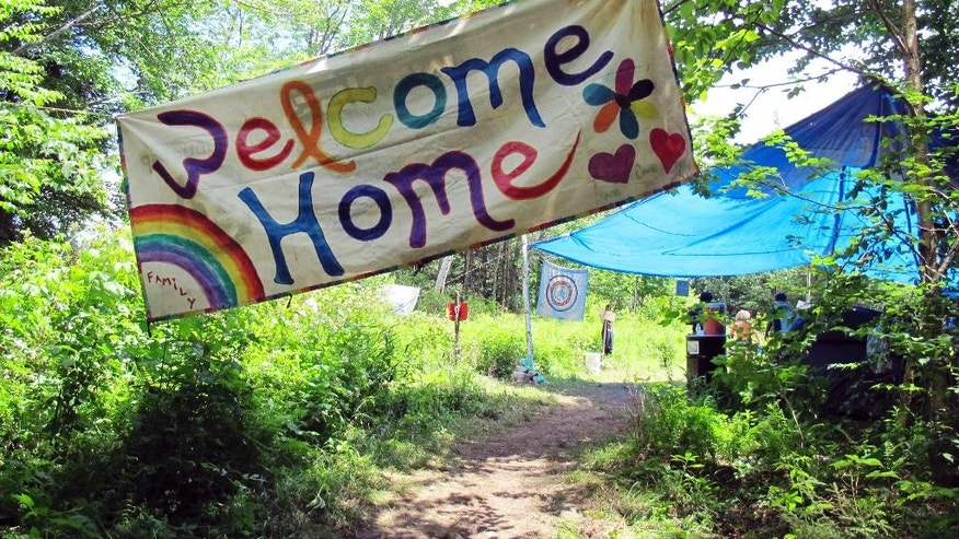 In this June 28, 2016 photo, a sign welcomes people to the gathering of the Rainbow Family of Living Light in Mount Tabor, Vt. People from across the country are flocking to the Green Mountain National Forest for the annual Rainbow Gathering of Living Light. (AP Photo/Wilson Ring)