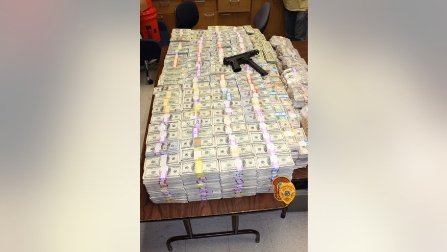 June 29, 2016: This image posted to Twitter by the Miami-Dade Police Department shows money and a Tec-9 handgun recovered from the home of a suspected marijuana trafficker. At least $24 million were recovered in a raid by police and federal agents.
