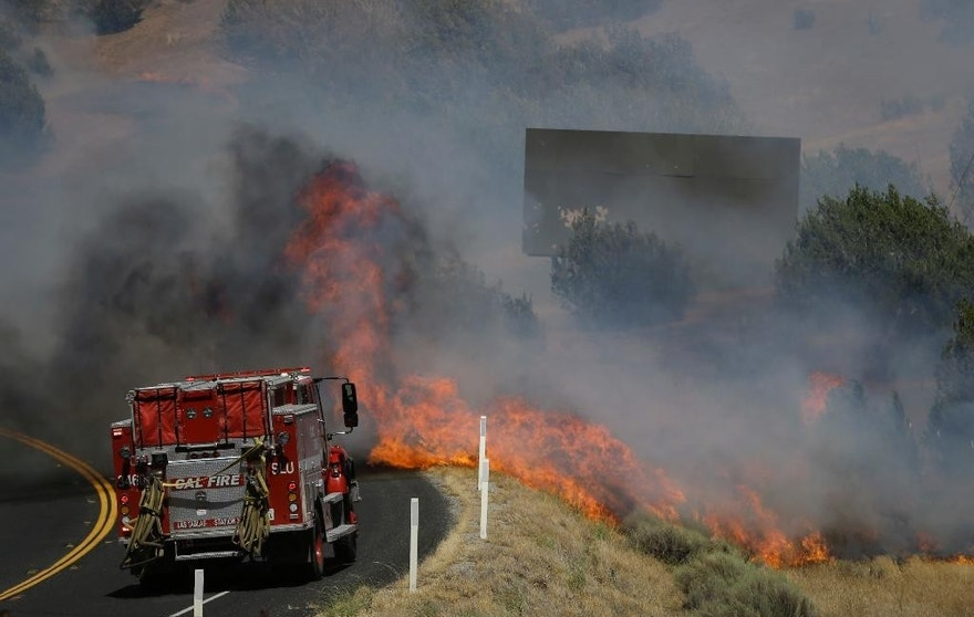 A flame from a wildfire approaches a fire truck as it moves along Highway 178 near Lake Isabella, Calif., Friday, June 24, 2016. The wildfire that roared across dry brush and trees in the mountains of central California gave residents little time to flee as flames burned homes to the ground, propane tanks exploded and smoke obscured the path to safety. (AP Photo/Jae C. Hong)