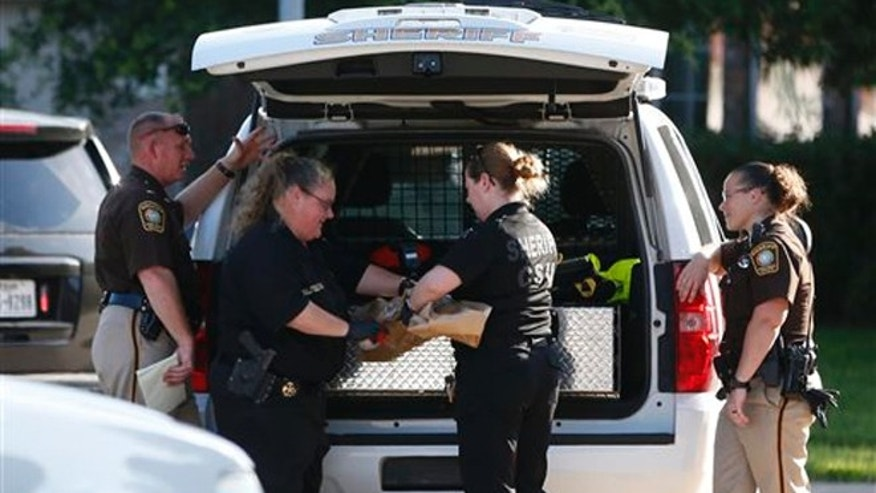 In this Friday, June 24, 2016 photo, Fort Bend County Sheriffs department crime scene members bag a gun for evidence in a shooting at Blanchard Grove and Remson Hollow in Katy, Texas.