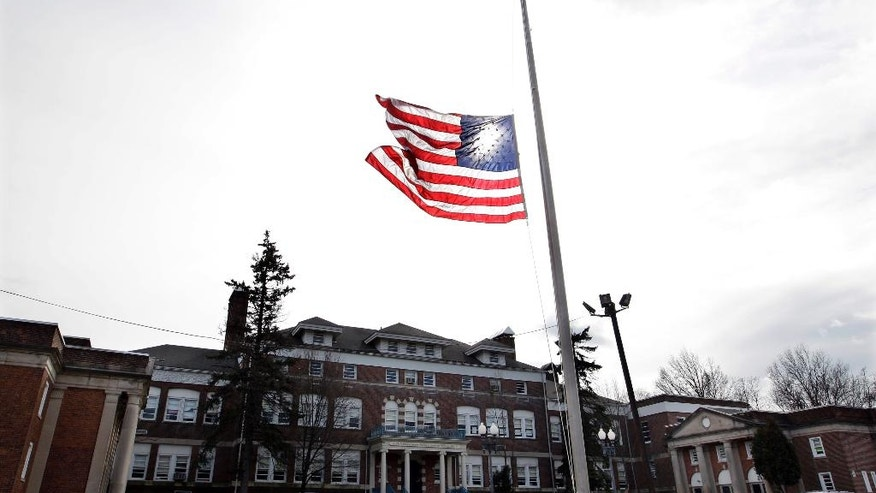 FILE- In this Feb. 12, 2012 file photo, an American flag flies at half-staff in front of the Whitney E. Houston Academy of Creative and Performing Arts in East Orange, N.J., to honor the performing artist Whitney Houston, who died the previous day. The honor once reserved for slain police officers, politicians and war heroes is more commonly extended to sports heroes and entertainers. (AP Photo/Mel Evans, File)