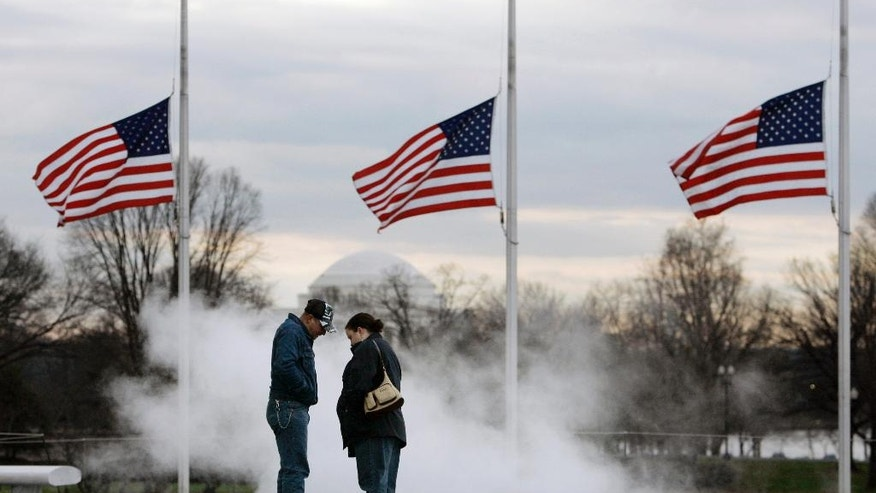 FILE- In this Dec. 27, 2006 file photo, James and Jennifer Florence, of Petersburg, Va., stand over a steam grate as flags fly at half staff at the Washington Monument in honor of former President Gerald Ford who died the previous day, in Washington. Presidents, senators and war heroes traditionally have been honored by lowering the American flag, but the honor has been extended to entertainers and sports heroes as well. (AP Photo/Gerald Herbert, File)