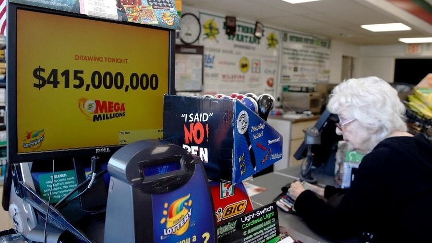 A customer, right, waits for her Mega Millions lottery ticket at a convenience store in Chicago, Friday, July 1, 2016. Friday night's Mega Millions drawing will give lottery players a shot at the 10th largest jackpot in U.S. history. (AP Photo/Nam Y. Huh)