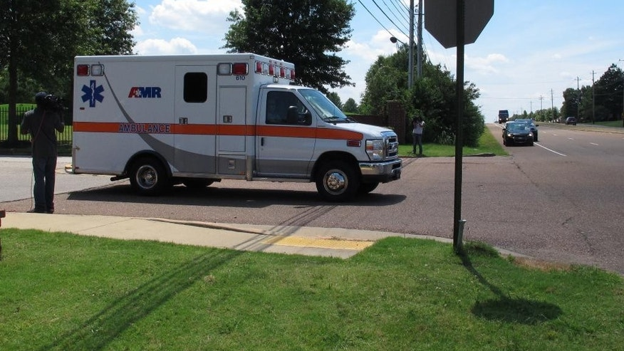 An ambulance leaves a gated neighborhood where four children were found stabbed to death Friday, July 1, 2016, in Memphis, Tenn. (AP Photo/Adrian Sainz)