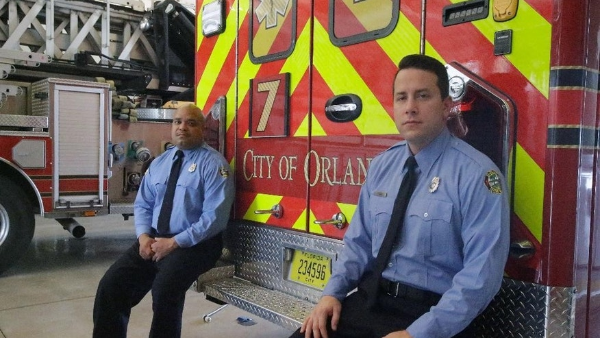 In this Thursday, June 30, 2016 photo, Josh Granada, right, and Carlos Tavarez the first paramedic-firefighters to respond to the Pulse nightclub shooting stand by their emergency vehicle at their fire station in Orlando, Fla. They made five trips with 13 victims to a hospital emergency room just a few blocks away the evening of the shooting.(AP Photo/John Raoux)