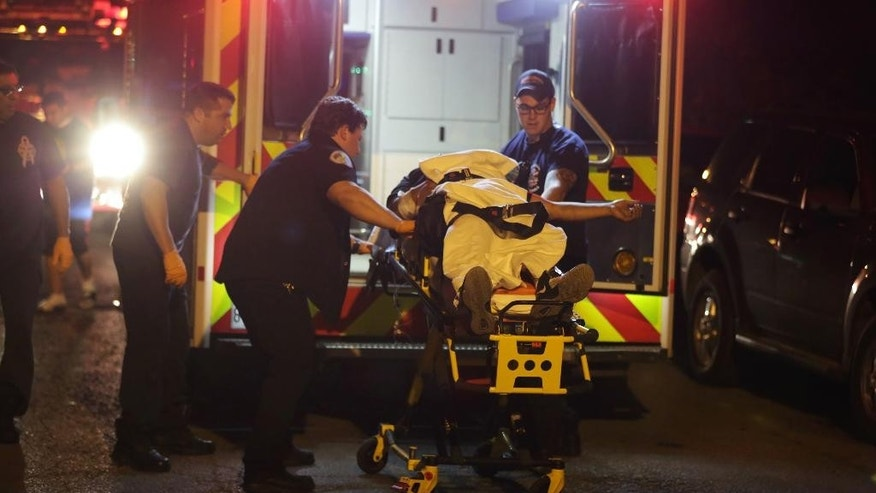 In this July 3, 2016 photo, a man is taken into an ambulance after a shooting in Chicago. Chicago police flooded the streets with thousands of officers and took dozens of gang members into custody over the July 4 weekend. Fewer people were shot to death, but more suffered gunshot wounds than over the same holiday weekend last year. (E. Jason Wambsgans/Chicago Tribune via AP)