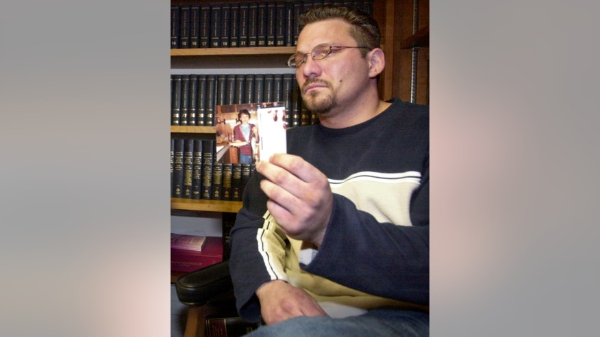 FILE – In this Feb. 6, 2003, file photo, Brian Gergely holds up an old photograph of himself while discussing a lawsuit against a priest and the Roman Catholic Diocese of Altoona-Johnstown, during a news conference in Altoona, Pa. Gergely, whose lawsuit was settled out of court in 2005, was found hanged Friday, July 1, 2016, at his home in Ebensburg, Pa., at the age of 46. (AP Photo/Keith Srakocic, File)