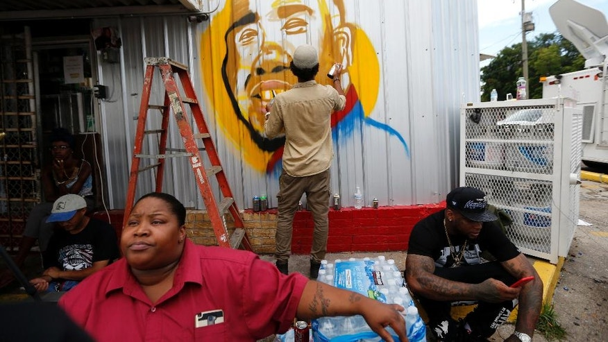 Artist Jo Hines spray paints a mural of Alton Sterling outside the Triple S convenience store in Baton Rouge, La., Wednesday, July 6, 2016. Sterling, 37, was shot and killed outside the store by Baton Rouge police, where he was selling CDs. (AP Photo/Gerald Herbert)