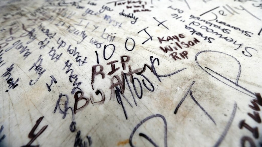 Messages of condolence are written on a table at a makeshift memorial for Alton Sterling, outside a convenience store in Baton Rouge, La., Wednesday, July 6, 2016.  Sterling was shot and killed by Baton Rouge police outside the store where he was selling CDs. (AP Photo/Gerald Herbert)