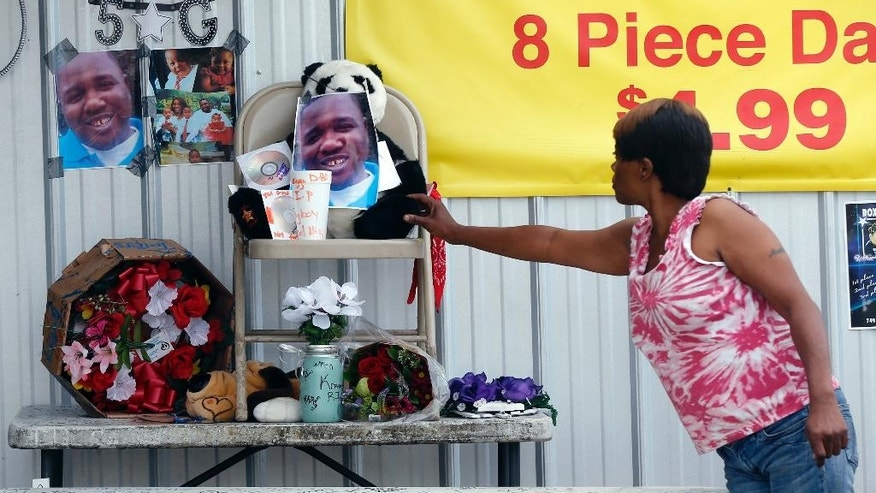 Nishka Johnson touches a makeshift memorial for Alton Sterling, outside a convenience store in Baton Rouge, La., Wednesday, July 6, 2016.   Sterling was shot and killed by Baton Rouge police outside the store where he was selling CDs. (AP Photo/Gerald Herbert)