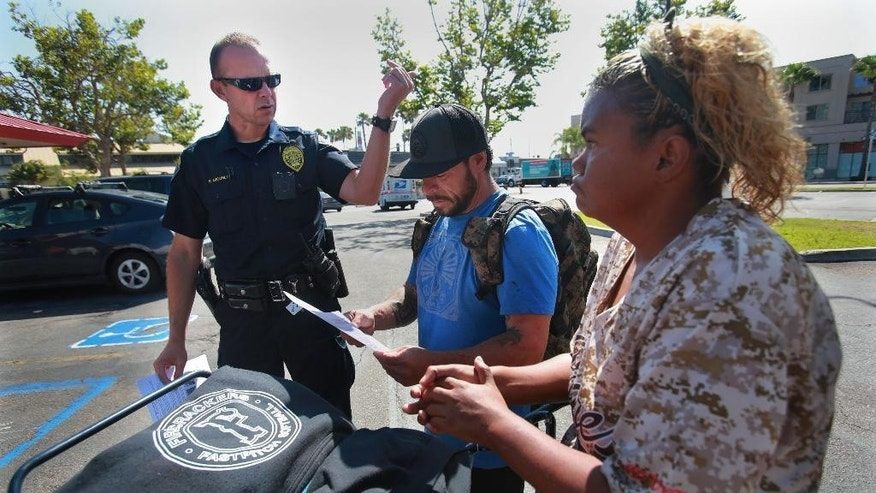 San Diego Homeless Outreach Team officer Brian Lucchesi canvasses several areas in the Midway and Sports Arena Blvd. area Wednesday, July 6, 2016, stopping to talk with people like Robert and Krista, two homeless people who stay in the area. The couple hadn't heard about the recent assaults on the homeless. On Wednesday, the San Diego Police Department's Homeless Outreach Team branched out to advise the area's homeless population about the increasing number of  assaults on homeless individuals. So far two people have been murdered and two others badly beaten.  (Peggy Peattie/San Diego Union-Tribune via AP)