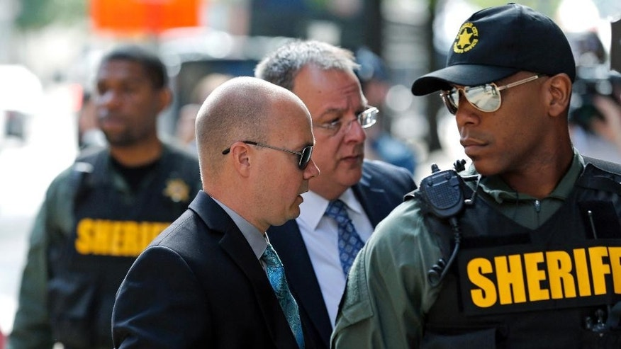 Lt. Brian Rice, second from left, one of the six members of the Baltimore Police Department charged in connection to the death of Freddie Gray, arrives at a courthouse for opening statements in his trial in Baltimore, Thursday, July 7, 2016. (AP Photo/Patrick Semansky)