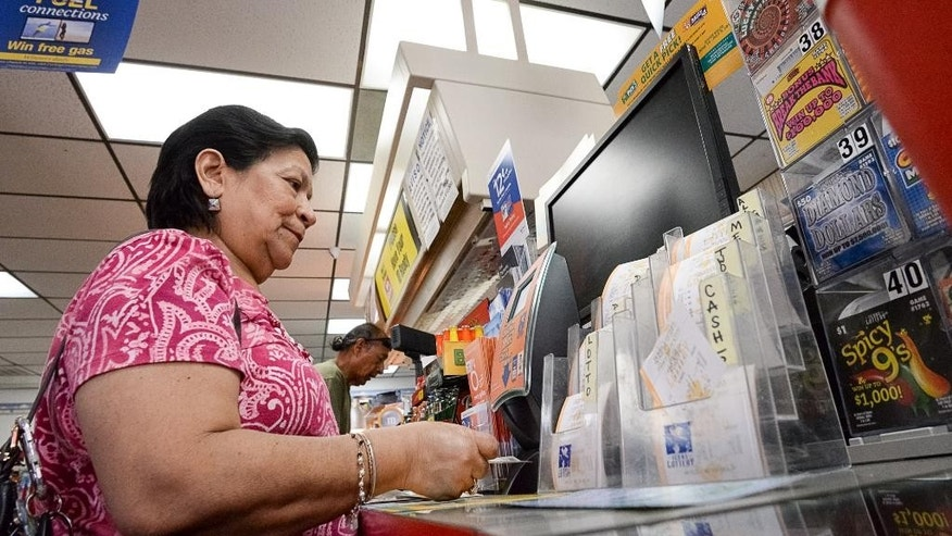 A woman checks old lottery tickets at a self-serve machine on Thursday, July 7, 2016, at the Alton Gloor Exxon gas station in Brownsville, Texas. Friday's drawing will be the 35th since Mega Millions had a winner — the longest rollover stretch in the game's history. Otto says that since the last winner in March, Mega Millions ticket sales have exceeded $1 billion. (Jason Hoekema/The Brownsville Herald via AP)