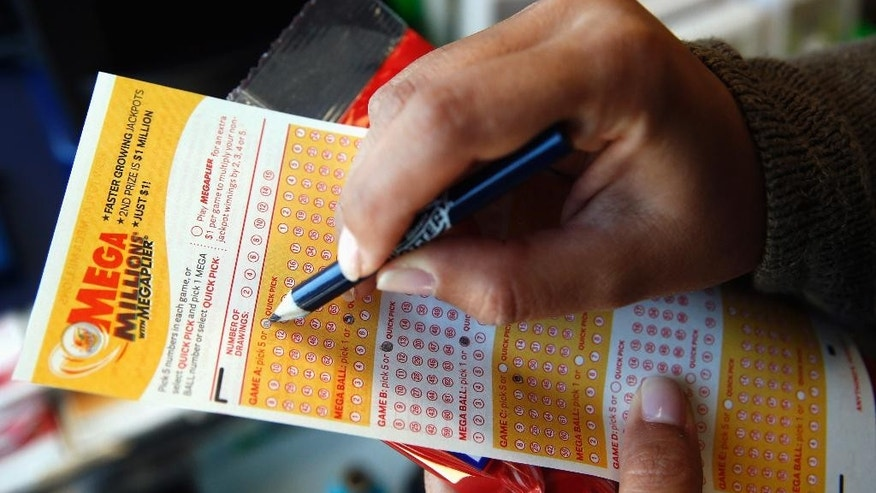 FILE - In this July 1, 2016. file photo, Sara Thompson picks numbers for the Mega Millions lottery at a convenience store in Chicago. The Mega Millions jackpot received a boost to over $500 million for the Friday, July 8 drawing after no one picked the right numbers Tuesday night. (AP Photo/Nam Y. Huh, File)