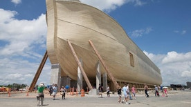Visitors pass outside the front of a replica Noah's Ark at the Ark Encounter theme park during a media preview day, Tuesday, July 5, 2016, in Williamstown, Ky. The long-awaited theme park based on the story of a man who got a warning from God about a worldwide flood will debut in central Kentucky this Thursday. The Christian group behind the 510 foot-long wooden ark says it will demonstrate that the stories of the Bible are true. Its construction has rankled opponents who say the attraction will be detrimental to science education. (AP Photo/John Minchillo)