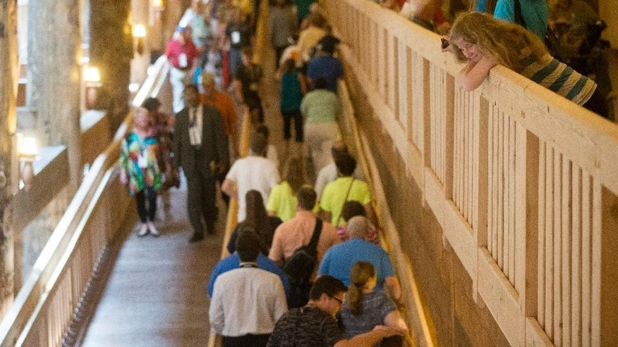 A visitor, right, smiles as foot traffic moves inside a replica Noah's Ark at the Ark Encounter theme park during a media preview day, Tuesday, July 5, 2016, in Williamstown, Ky. The long-awaited theme park based on the story of a man who got a warning from God about a worldwide flood will debut in central Kentucky this Thursday. The Christian group behind the 510 foot-long wooden ark says it will demonstrate that the stories of the Bible are true. Its construction has rankled opponents who say the attraction will be detrimental to science education. (AP Photo/John Minchillo)