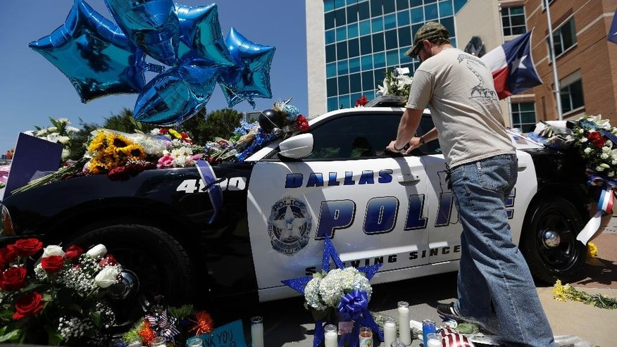 Michael O'Mahoney, a former police officer, places his patch on a make-shift memorial at the Dallas police headquarters, Friday, July 8, 2016, in Dallas. Five police officers are dead and several injured following a shooting in downtown Dallas Thursday night. (AP Photo/Eric Gay)