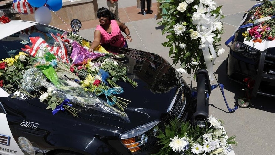 Cynthia Ware places flowers on a make-shift memorial at the Dallas police headquarters, Friday, July 8, 2016, in Dallas. Five police officers are dead and several injured following a shooting in downtown Dallas Thursday night. (AP Photo/Eric Gay)