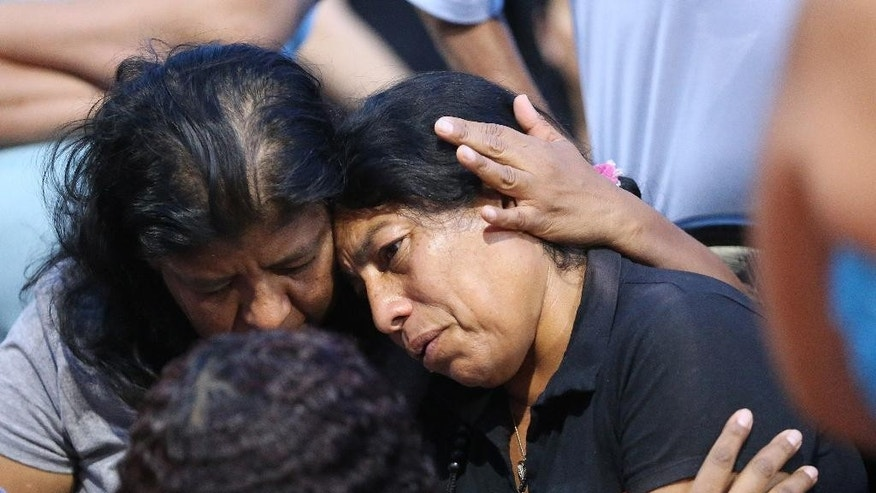 Maria Izazaga, mother of Abril Izazaga and Jose Izazaga, is comforted during a vigil in Midvale, Utah, on Thursday, July 7, 2016. A man accused of gunning down the teenagers during an argument over a T-shirt at a suburban Salt Lake City apartment complex is under arrest as family members mourn the senseless killing of siblings who shared a tight bond. (Jeffrey D. Allred/Deseret News via iAP)