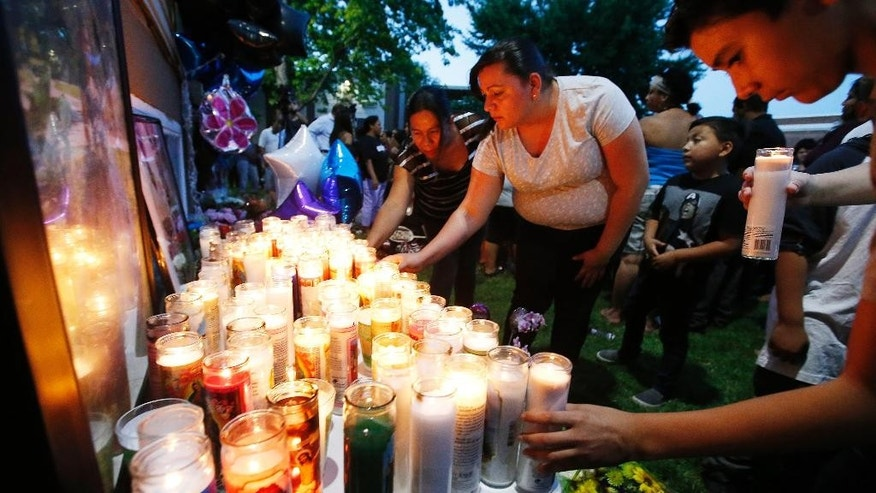 Candles are lit and placed near photos during a vigil for Abril Izazaga and her brother Jose Izazaga in Midvale, Utah, on Thursday, July 7, 2016. A man accused of gunning down a teenage brother and sister during an argument over a T-shirt at a suburban Salt Lake City apartment complex is under arrest as family members mourn the senseless killing of siblings who shared a tight bond. (Jeffrey D. Allred/Deseret News via AP)