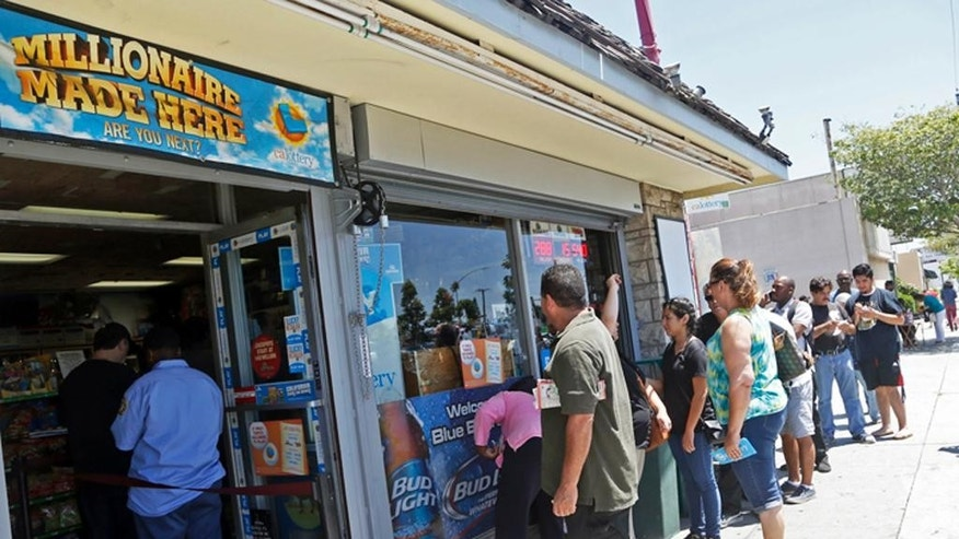 People line up outside Bluebird Liquors in Hawthorne, Calif., to buy lottery tickets Friday afternoon, July 8, 2016. The Mega Millions jackpot for Friday's drawing has soared to over $500 million. (AP Photo/Nick Ut)